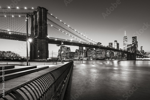 Obraz Brooklyn Bridge Park boardwalk in evening with the skyscrapers of Lower Manhattan, East River, and the Brooklyn Bridge in Black & White. Brooklyn, New York City - fototapety do salonu
