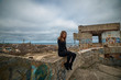 Young slim brunette on a ruins of abandoned building
