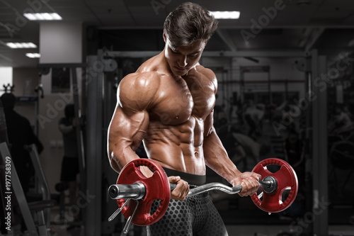 Fotografia Muscular man working out in gym doing exercises with barbell at biceps, strong m