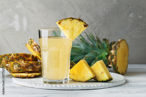 Pineapple fresh juice in glass on a wooden table