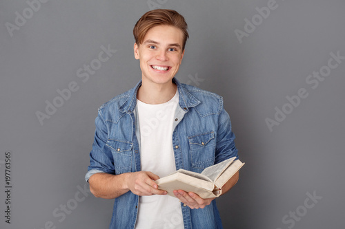 Fototapety, obrazy: Young man student in jeans jacket studio isolated on grey reading book joyful