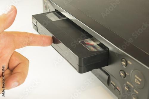 insert a videotape into a tape recorder Fototapet