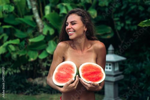 Fotografie, Obraz  Portrait beautiful brunette girl in swimsuit with watermelon fruit holding in hands