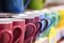 Set Of Colorful Mug Cups On A Old Wooden Table, Blurred Background