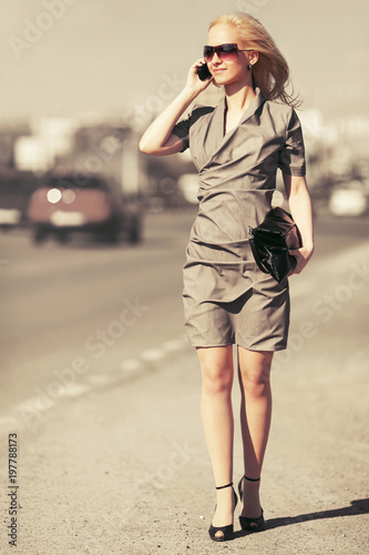 Young fashion blond woman calling on cell phone walking in city street Poster