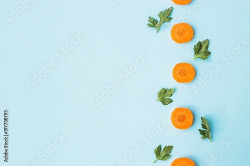 Bright round ringlets of carrots with green parsley sprigs on a blue background. Top view, flat lay. Copyspace