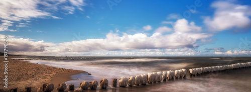 Obraz Panorama of a beautiful winter landscape with frozen wooden breakwater at the Baltic Sea. Concept holidays and travel - fototapety do salonu