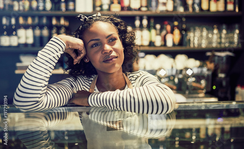 Fotografía  Young African entrepreneur leaning on her cafe counter thinking