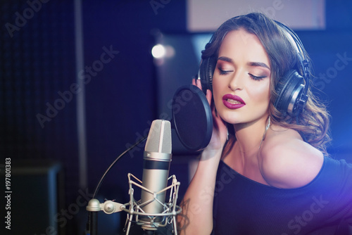 Beautiful young singer who recorded a song in a professional recording studio Fotobehang