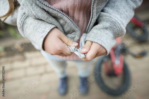 Photo パーカーのジッパーを閉める子供の手