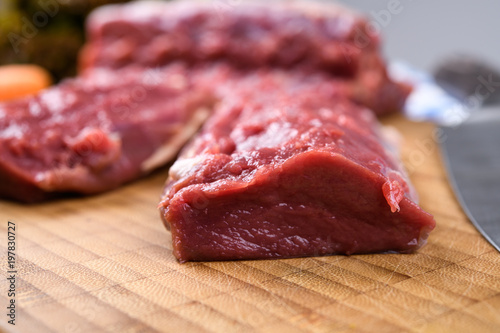 saddle of venison on wooden board