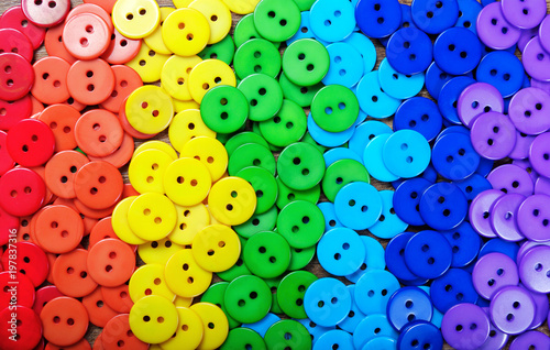 Poster Macarons Colors of rainbow. Pattern of multicolored buttons texture background. Palette of rainbow colors. Multicolored buttons on a wooden table.