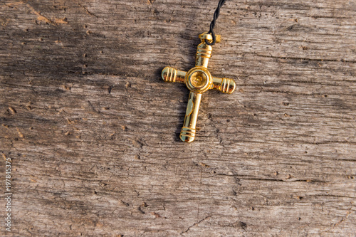 Small Christian golden cross on rustic wooden background Canvas Print