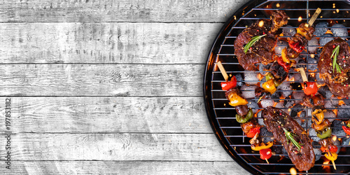 Spoed Foto op Canvas Grill / Barbecue Top view of fresh meat and vegetable on grill placed on wood