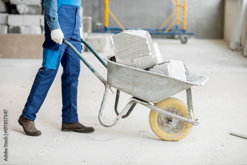 Fotografía  Builder carrying blocks on a wheelbarrow at the construction site indoors