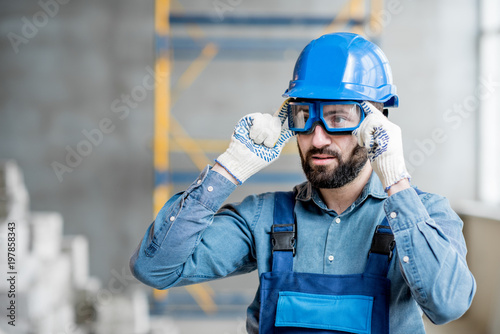 Fototapeta Close-up portrait of a handsome bearded builder with protective glasses and helmet indoors obraz