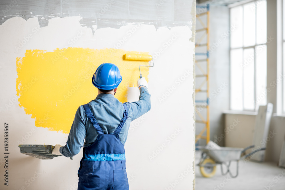 Fototapety, obrazy: Workman in uniform painting wall with yellow paint at the construction site indoors