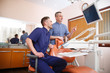 Two doctors in blue uniform in a dentist's office.