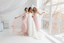 Happy Bridesmaid Hugging The Bride Covered By Veil In The Bedroom In The Morning, Having Fun.