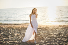 Beautiful Girl Bride In A White Dress And Sneakers, At Sunset Walks Along The Beach.
