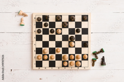 Top view on wooden chess board with figures during the game on white wooden tabl Canvas Print