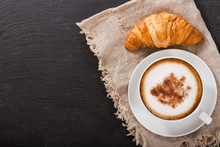 Cup Of Cappuccino Coffee And Croissant On Dark Table