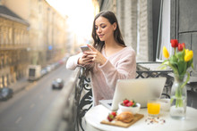 Young Woman Sitting In The Balcony, Checking Her Phone While Having Breakfast
