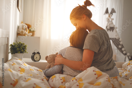 Photo  morning awakening. mother wakes her daughter in bed in morning