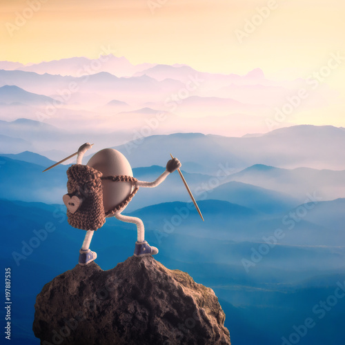 Easter egg with raised hands standing on a mountain top