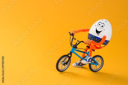 Funny Easter egg sitting on a miniature bicycle