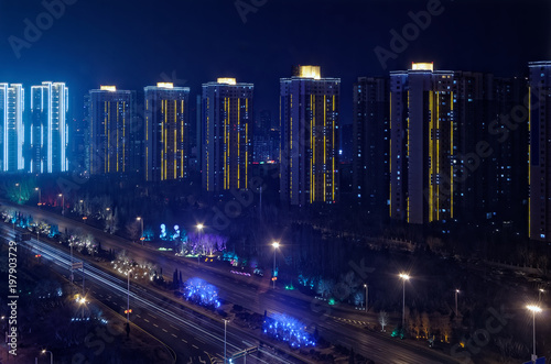 Valokuva  Illuminated modern skyscraper buildings at the motorway by night, Shenyang, Chin