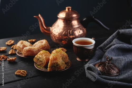 Turkish traditional Dessert Baklava with tea on dark background Wallpaper Mural