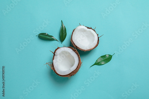 Coconut halves with leaves on color background
