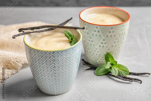 Fotografia Vanilla pudding, sticks and fresh mint on table