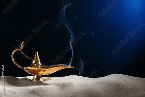 Aladdin magic lamp on sand against dark background Wallpaper Mural
