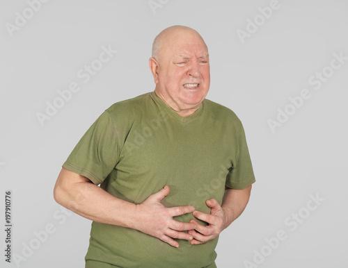 Valokuvatapetti Senior man suffering from pain in stomach on light background