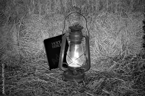 Photo  Black and white picture of a bible beside a lantern sitting on a bale of hay