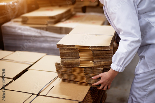 Fotografía  Close up of young female worker picking up stacks of folded cardboard boxes from a bigger stack in factory storage room