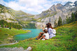 Leinwandbild Motiv young happy family of tourists photographing nature, beautiful blue natural lake oeschinensee, in Switzerland, a fantastic mountain landscape overlooking the water and forest