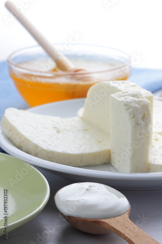 Poster Produit laitier Cheese pattern, honey and sour cream, feta in white and green plate, soft cheese on a white background, wooden spoon with sour cream, French breakfast, blue napkin, honey in glassware