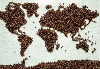 Fototapeta Kawa The world map from coffee beans on a light concrete background