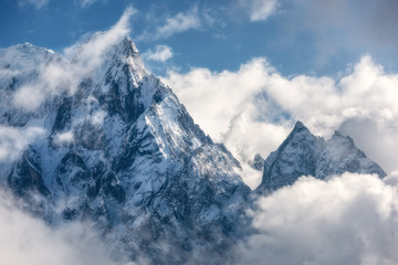 Fototapeta Góry Majestical scene with mountains with snowy peaks in clouds in Nepal. Landscape with beautiful high rocks and dramatic cloudy sky in sunny bright day. Nature background. Vintage. Amazing Himalayas