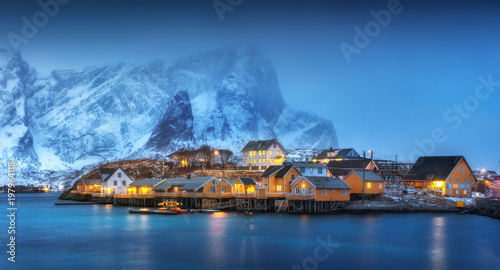Foto auf Gartenposter Skandinavien Beautiful yellow rorbuer and houses in Sarkisoy village, Lofoten islands, Norway. Winter landscape with traditional norwegian rorbuer, sea, snowy mountains in fog at night. Old fishermen's houses