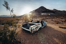 Old Rusty Abandoned Car In The Desert At Sunset Time