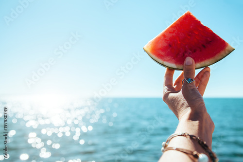 Canvas Prints Boho Style Watermelon slice in woman hand over sea