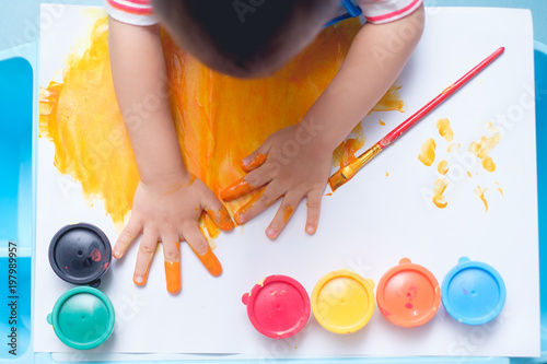 Bird eye view / Top view of little Asian 18 months / 1 year old toddler baby boy child finger painting with hands and watercolors, kid painting at home, Creative play for kids and toddlers concept
