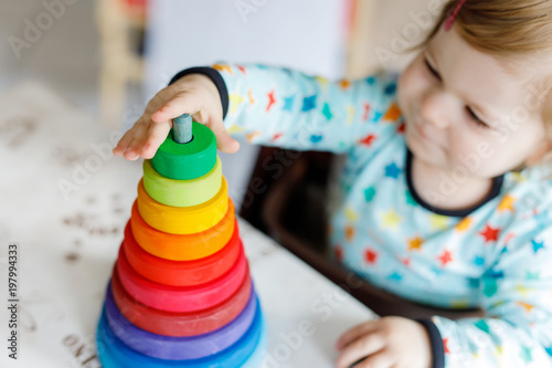 Obraz Adorable cute beautiful little baby girl playing with educational wooden rainbow toy pyramid - fototapety do salonu