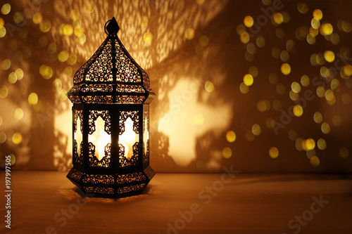 Ornamental Arabic lantern with burning candle glowing at night and glittering golden bokeh lights Canvas Print