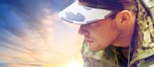 Army, National Service And People Concept - Close Up Of Young Soldier In Military Uniform Over Sky Background