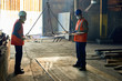 Full length portrait of two factory workers moving metal part in workshop, copy space